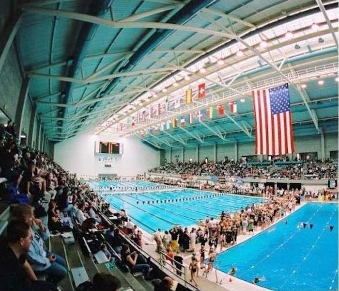 Swimming pools with people sitting in the stands and standing next to the pool